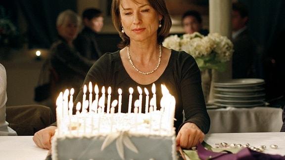 Melancholisch aber gelassen schaut Giulia (Corinna Harfouch) sich ihren Geburtstagskuchen mit den 50 Kerzen an.