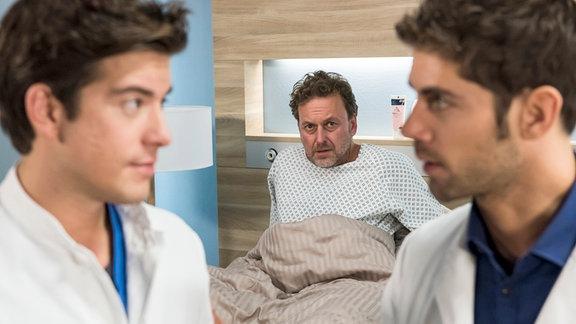 """Niklas (Roy Peter Link, r.) rügt Ben (Philipp Danne, l.) für die """"Konfrontationstherapie"""" an seinem Angstpatienten Theo Ortlieb (Thomas Schmuckert, M.)."""