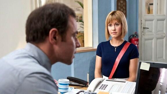 Klara Degen (Wolke Hegenbarth, r.) berichtet Hauptkommissar Paul Kleinert (Felix Eitner, l.), was sich im Büro ihres ermordeten Chefs abgespielt hat. Kleinert, dessen Sekretärin im Mutterschutz ist, plagt sich mit dem Computer.