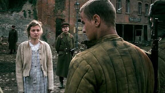 Greta (Fabienne Haller) soll ihren Peiniger (Tigran Petrosyan, 2.v.r.) an Fjodorow (Vladislav Grakovskiy, 3.v.r.) verraten.