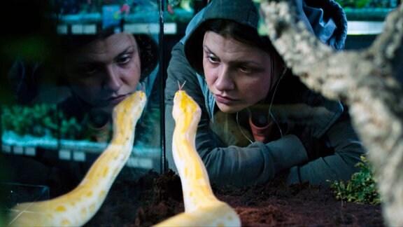 Das Mädchen (Jessy Moravec) beobachtet eine Schlange.