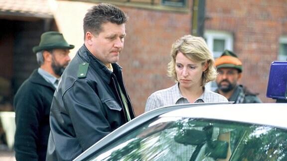 Dorfpolizist Schulz (Bruno F. Apitz) geleitet die verstörte Birgit Sofsky (Kirsten Block), die gerade ihren Mann beim Jagdunfall verloren hat, nach Hause.