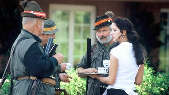 Simone Körner (Isabella Jantz, r.) reicht den Jägern Erfrischungen vor der Jagd und genießt dabei die Blicke der Männer.