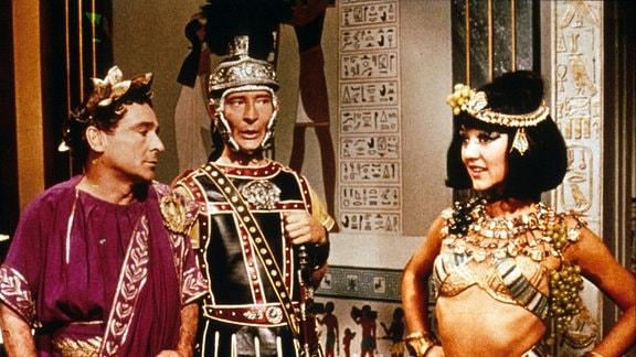 Julius Cäsar (Kenneth Williams, Mitte) mit seinem Leibwächter Hengist (Kenneth Connor, r.) zu Besuch bei Kleopatra (Amanda Barrie).