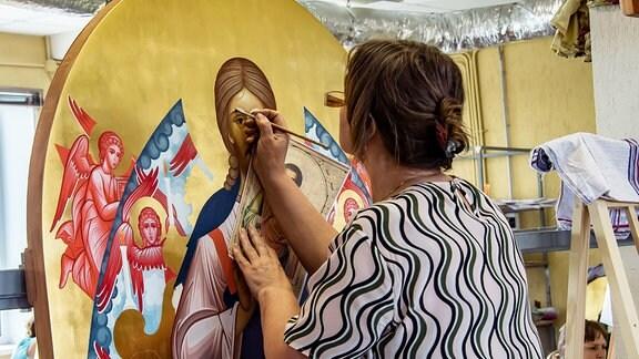 Eine Künstlerin bei der Arbeit an einer Ikone. Palech ist das Zentrum für Ikonostasen und Ikonenbilder.