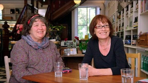 Zwei Frauen sitzen an einem Tisch.