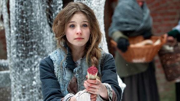 Inga (Lea Müller) muss Schwefelhölzer auf dem Markt verkaufen.