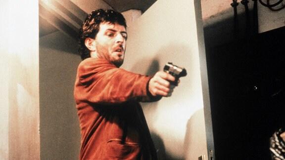 Der Amsterdamer Kommissar Eric (Huub Stapel) mit einer Handfeuerwaffe.