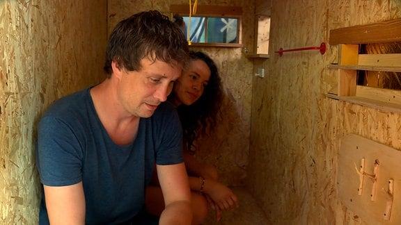 Sven Lüdecke und eine ehrenamtliche Helferin bringen ein Regal an der Wand an. Auf 3,20 Quadratmetern ist die mobile Wohnbox im Idealfall ein Übergang zu einer festen Wohnung.
