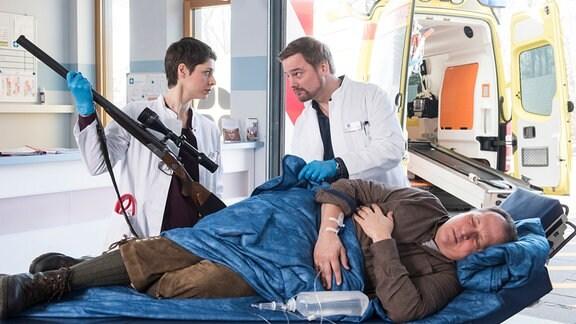 Waldemar König (Thomas Kügel, v.) wird mit einer Schussverletzung ins JTK geliefert. Dr. Theresa Koshka (Katharina Nesytowa, l.) und Dr. Marc Lindner (Christian Beermann, h.r.) kümmern sich um den Jäger.