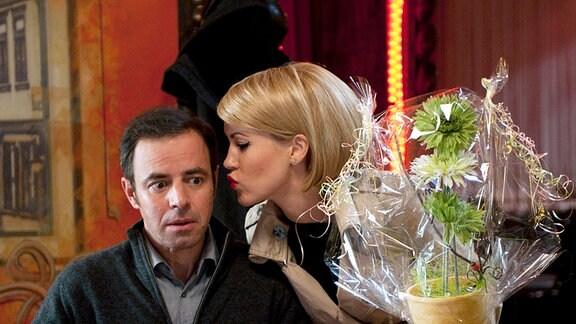 Klara (Wolke Hegenbarth, M.) kommt mit einem Blumentopf bewaffnet zu einem Abendessen zu Paul Kleinert (Felix Eitner, l.) und dessen Mutter Hermine Kleinert (Karin Schröder, r.). Klaras Chef will, dass sie seine Freundin mimt.