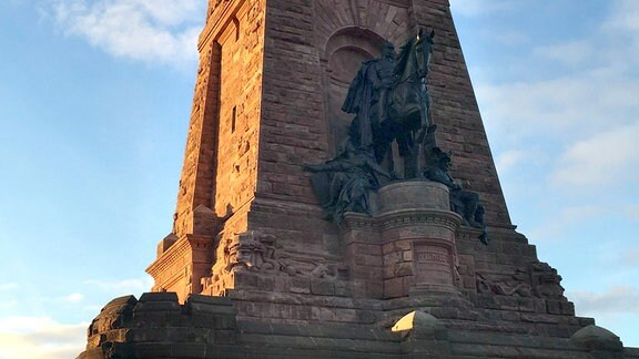 Südöstlich vom Harz liegt eines der kleinsten Gebirge Deutschlands – 7 km breit und 19 km lang – das Kyffhäusergebirge. Weithin sichtbar ein riesiges Denkmal, frühes Symbol des deutschen Nationalstaates und Fortschreibung des Mythos um den sagenumwobenen Kaiser Barbarossa.