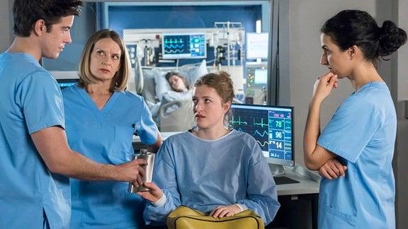 Frederike (Lola Klamroth, 2.v.r.) gesteht den Ärzten Ben Ahlbeck (Philipp Danne, l.), Dr. Franziska Ruhland (Gunda Ebert, 2.v.l.) und Dr. Leyla Sherbaz (Sanam Afrashteh, r.), dass sie eventuell Schuld an dem Zustand ihrer Schwester (Muriel Bielenberg, h.) ist.