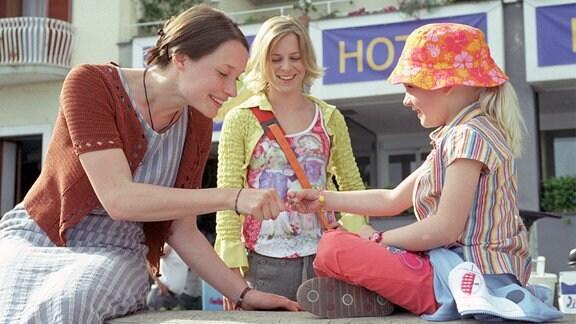 Barbaras Töchter und Enkelin genießen in einer italienischen Stadt die Sonne.
