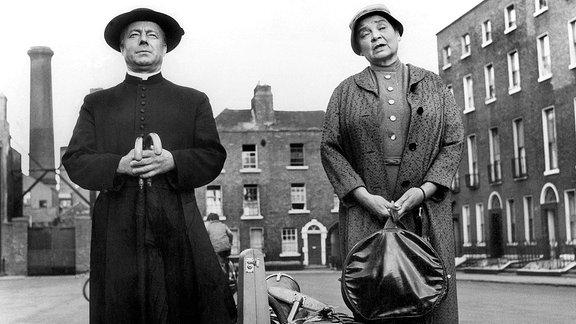 Pater Brown (Heinz Rühmann, li.) ist mit seiner Haushälterin Mrs. Smith (Lina Carstens) in seiner neuen Gemeinde angekommen.