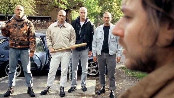 Eine Gruppe Neonazis droht Stefan Mayer mit Baseballschlägern.