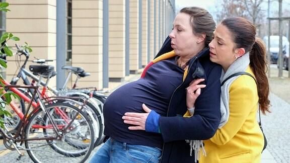Oberschwester Arzu (Arzu Bazman, re.) fällt vor Dienstbeginn eine hochschwangere Frau auf, der es nicht gut zu gehen scheint. Nadine Vollmer (Viktoria Gabrysch, li.) sagt, sie sei erst in der 29. Woche und es sei alles gut. Doch plötzlich wird Nadine schwindelig und Arzu muss sie auffangen.