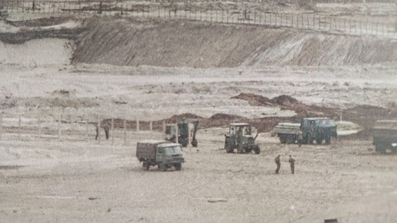 Laster und Bagger rollen durch den staubigen Tagebau.