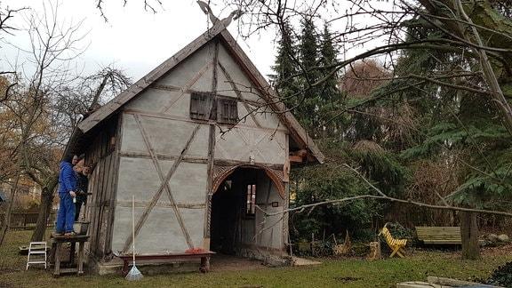 Die kleine, unverputze Fachwerk-Scheune steht jetzt im weitläufigen Garten der Küglers. Udo Kügler und Schwiegersohn Tim arbeiten gerade an der Außenwand.