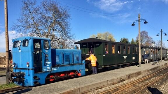 Die Bergwerksbahn ist eine historische Eisenbahn mit hellblauer Lok und drei schwarzen Waggons.