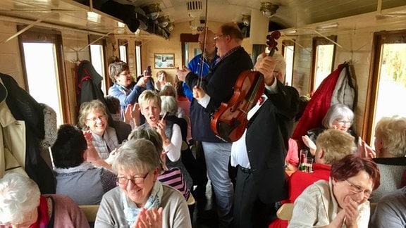 Im Inneren der Bahn sitzt gut ein Dutzend gut gelaunter Senioren, ausgelassen zu einem Musiker-Duo mit Geige klatschend und mit Sekt auf dem Tisch.