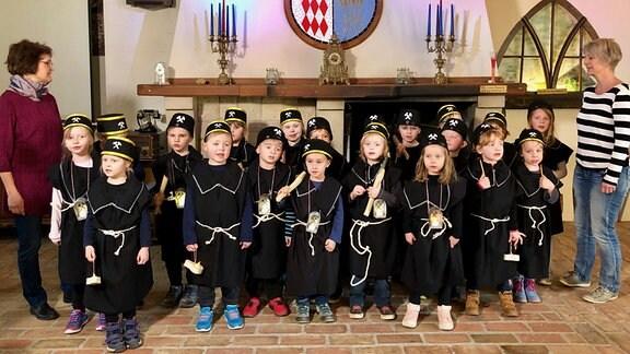 Ein gutes Dutzend Kinder hat sich in Choraufstellung positioniert. Die Kinder tragen schwarze, sackartige Kleider und schwarze Mützen mit zwei gekreuzten Hämmern - traditionelle Bergbauuniform.