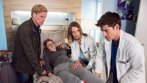 Dr. Franziska Ruhland (Gunda Ebert, 2.v.r.) und Ben Ahlbeck (Philipp Danne, r.) wundern sich, dass Pia (Katharina Stark, 2.v.l. mit Gunnar Teuber, l.) plötzlich ohnmächtig wird.