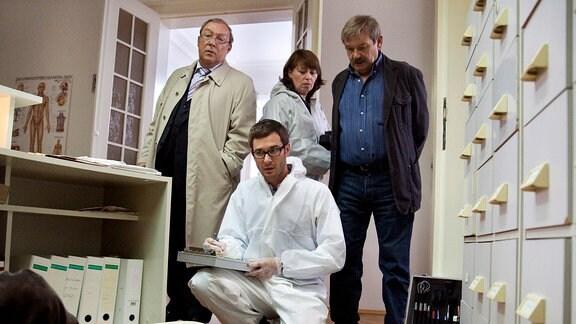 Dr. Stabroth (Jochen Schropp, vorn knieend) gibt Schmücke (Jaecki Schwarz, links), Schneider (Wolfgang Winkler, rechts) und Frau Weigand (Marie Gruber, hinten Mitte) nach der Untersuchung der Leiche eine erste Einschätzung.
