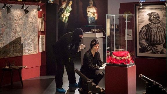 Tjard Theissen (Peter Benedict, l.) und Nadine Dorn (Annika Martens, r.) wollen eine wertvolle Störtebeker-Kette aus dem Lübecker Hansemusemum stehlen.