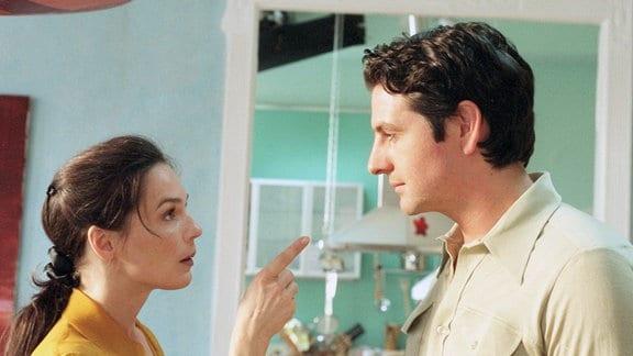 Eine Frau zeigt mit dem ausgestreckten Zeigefinger auf einen Mann. Ihre Mimik verrät ihre Wut.
