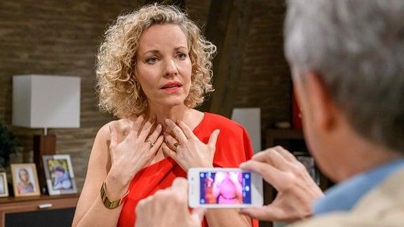 André (Joachim Lätsch, r.) fotografiert Natascha (Melanie Wiegmann, l.) in deren Kleid, für den Auftritt im Stadion. Doch plötzlich steht Natascha vor einem ernsten Problem.