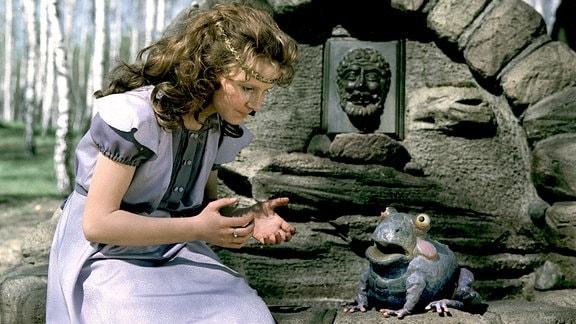 Prinzessin Henriette sitzt am Brunnen, gegenüber von dem Frosch.