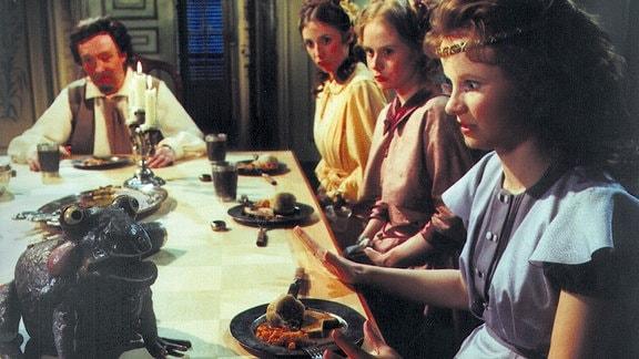 Der Frosch sitzt auf dem Tisch. Prinzessin Henriette schaut ihn entsetzt an.