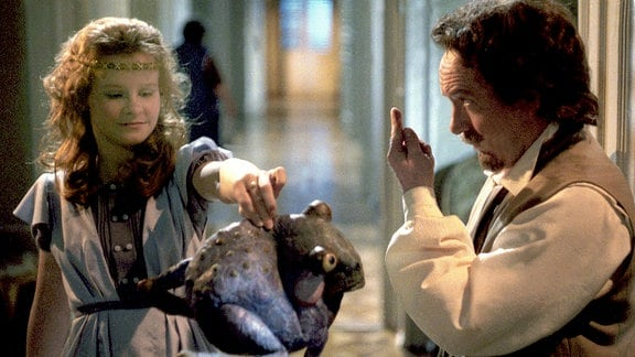 Die Prinzessin hält den Frosch angewidert von sich weg. Der König steht mit gehobenem Zeigefinger vor ihr.
