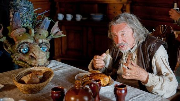 Der Drache Drako hilft dem Großvater (Karel Gott) in der Schmiede - und beim Essen.