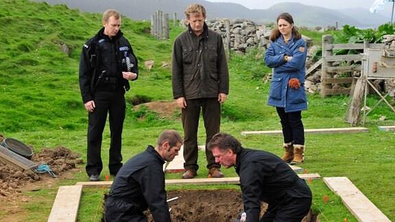 Zusammen mit seinen Kollegen Sandy Wilson (Steven Robertson, stehend li.) und Alison McIntosh (Alison O'Donnell, re.) kommt Detective Inspector Jimmy Perez (Douglas Henshall, Mitte) einem düsteren Geheimnis auf die Spur.