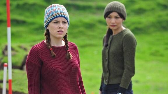 Archäologin Hattie James (Gemma Chan, re.) und Doktorandin Sophie (Sophie Rundle) haben auf dem Grundstück der alten Mima einen menschlichen Schädelknochen gefunden.