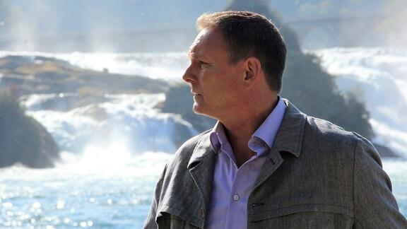 Axel Bulthaupt steht vor einem Wasserfall.