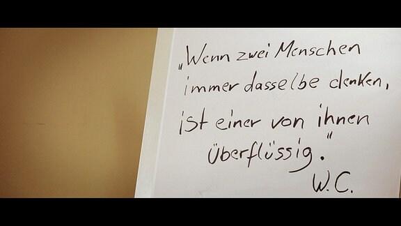 """Zettel mit handschriftlicher Aufschrift: """"Wenn zwei Menschen immer dasselbe denken, ist einer von ihnen überflüssig. W.C."""""""