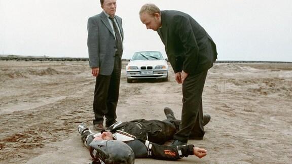 Regungslos liegt Robert Quint (Ralph Herforth) im Sand - das Ende einer Verfolgungsjagd mit dem Motorrad. Kommen die Kommissare Ehrlicher (Peter Sodann, rechts) und Kain (Bernd Michael Lade) zu spät?
