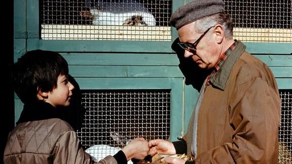 Friedhelm Kunze (Rolf Herricht) steht mit einem Jungen vor einem Kaninchenstall.