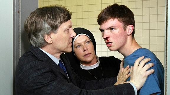 Der Rektor (Lutz Blochberger, l.) und Schwester Hanna (Janina Hartwig, M.), kümmern sich um Kai (Leander Butz, r.), dem Sarah die Nase blutig geschlagen hat.