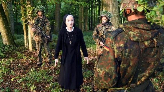 Schwester Agnes (Emanuela von Frankenberg, M.) fällt fast in Ohnmacht, als sie beim Kräutersammeln im Klosterwald plötzlich auf Soldaten trifft (mit Komparsen).