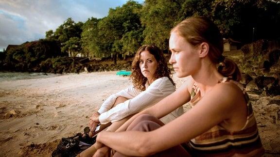 Filipa (Anja Knauer, l.) und Daniels Frau Jenny (Inez Bjørg David) sitzen am Strand