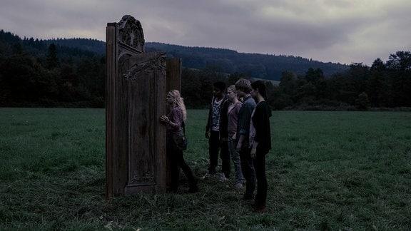 Die Jugendlichen öffnen eine star verzierte Tür, die mitten auf einer Wiese steht.