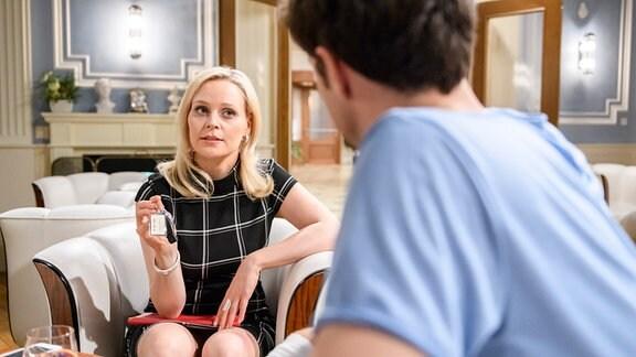 Annabelle (Jenny Löffler, l.) übergibt Joshua (Julian Schneider, r.) scheinbar großzügig das Beweismaterial, das sie gegen ihn in der Hand hat.