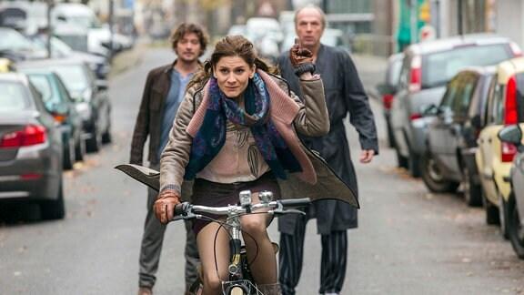 Helene Dumont (Christina Hecke) fährt mit dem Rad davon
