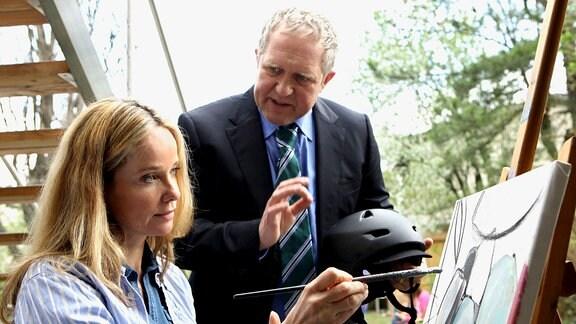 Henni Fischbach (Ann-Kathrin Kramer),malt an einer  Staffelei;Hubert Fischbach (Harald Krassnitzer) spricht mit ihr.