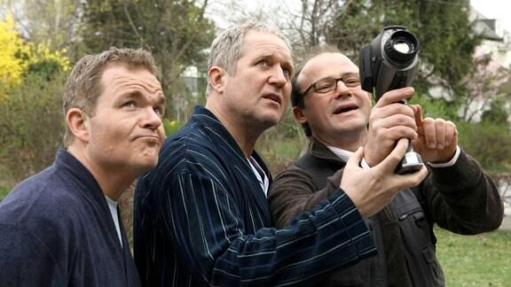 Viktor Fischbach (Cornelius Obonya, links), Hubert Fischbach (Harald Krassnitzer, Mitte) und Rüssler (Gerhard Liebmann)  - mit einer Kamera - blicken nach oben.