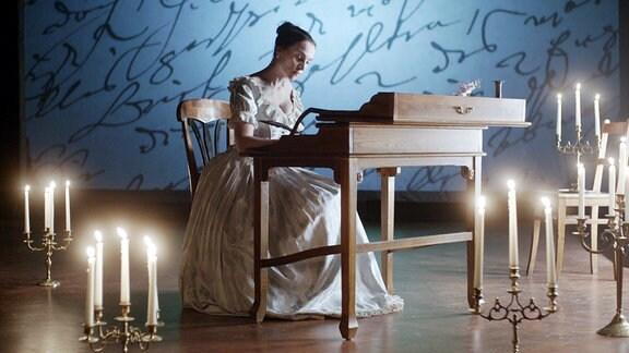Clara Schumann (Jana Klinge), an einem klkeinen Sekretär sitzend und schreibend.